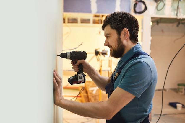 Zijaanzicht portret van bebaarde bouwvakker boormuur tijdens het renoveren van huis alleen, kopie ruimte
