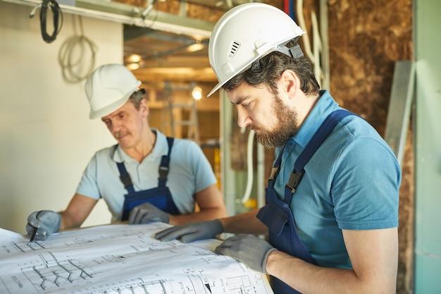 Zijaanzicht portret van bebaarde bouwvakker veiligheidshelm dragen tijdens het kijken naar plattegronden tijdens het renoveren van huis, kopie ruimte
