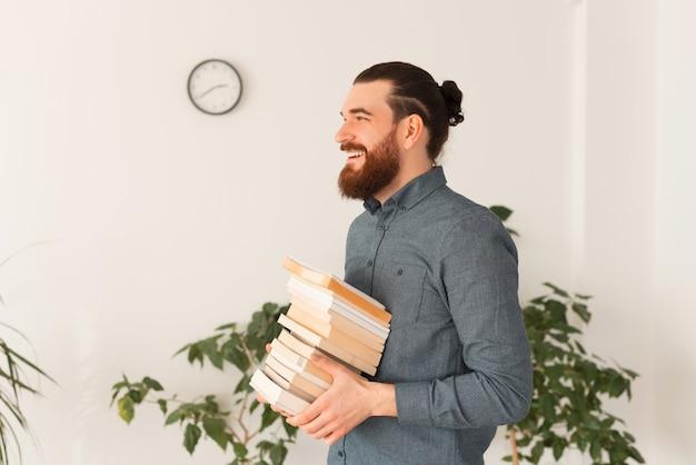 Zijaanzicht portret van bebaarde man met boeken in kantoor