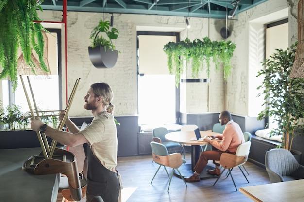 Zijaanzicht portret van bebaarde werknemer die meubels in café regelt terwijl hij zich voorbereidt op opening in de ochtend, kopieer ruimte