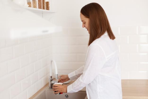 Zijaanzicht portret van donkerharige vrouw afwas of gietbeker met vers drinkwater bij de keukenkraan, vrouw met een wit casual stijl shirt, poserend in de keuken.
