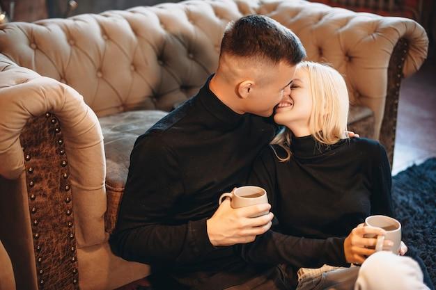 Zijaanzicht portret van een aantrekkelijke jonge man en vrouw die plezier glimlachen terwijl ze thuis op de vloer zitten en warme koffie drinken.