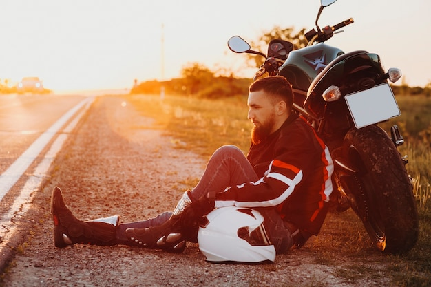 Zijaanzicht portret van een bebaarde zelfverzekerde man zittend op de grond en leunend op zijn fiets ernstig neerkijkend met een hand op zijn helm terwijl hij aan de kant van de weg rust tijdens zijn fietstocht.