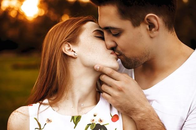 Zijaanzicht portret van een geweldig jong koppel kussen tegen zonsondergang met gesloten ogen terwijl man het gezicht van zijn vriendin aanraakt.