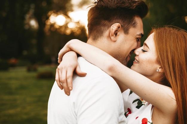 Zijaanzicht portret van een geweldig paar omarmen en glimlachen voordat ze kussen met gesloten ogen tegen zonsondergang in de stad.