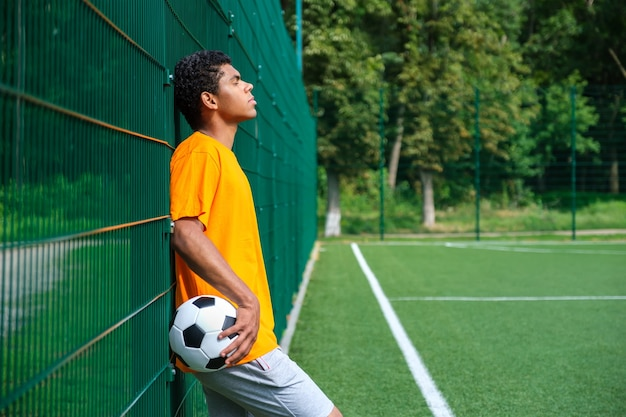 Zijaanzicht portret van een jonge afro-amerikaanse man die voetbal vasthoudt terwijl hij met zijn rug tegen het hek staat in het sportveld buiten, kopieer ruimte