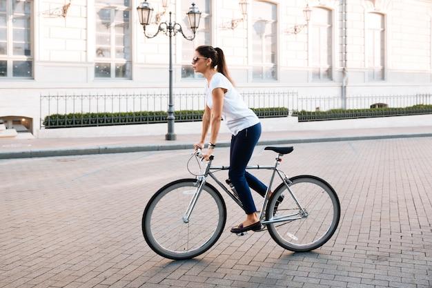 Zijaanzicht portret van een jonge mooie vrouw rijden op de fiets in de stad straat