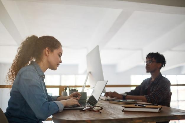 Zijaanzicht portret van een jonge vrouw met behulp van laptop tijdens het werken aan de balie in softwareontwikkelingsbureau met afro-amerikaanse collega code schrijven op achtergrond, kopie ruimte