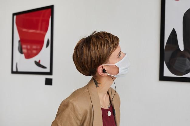 Zijaanzicht portret van een jonge vrouw schilderijen kijken en dragen masker op moderne kunst galerie tentoonstelling,