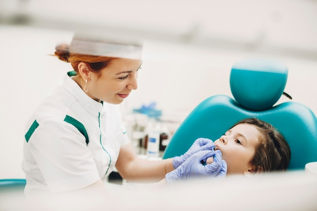 Zijaanzicht portret van een mooi klein kind met een tandoperatie in een pediatrische stomatologie. jonge pediatrische tandarts die een tandonderzoek doet.
