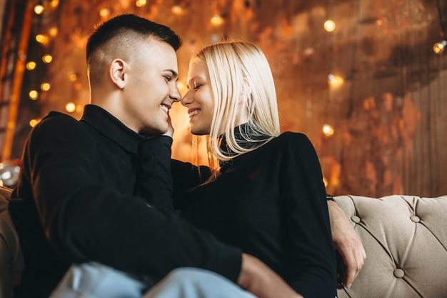 Zijaanzicht portret van een mooie jonge paar zittend op de bank omarmen