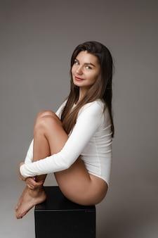 Zijaanzicht portret van een mooie jonge vrouw met lang sluik bruin haar omhelst haar benen zittend op blote voeten op zwarte kubus, glimlachend in de camera.