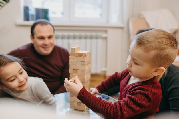 Zijaanzicht portret van een mooie kleine jongen serieus spelen in een spel met zijn zus thuis.