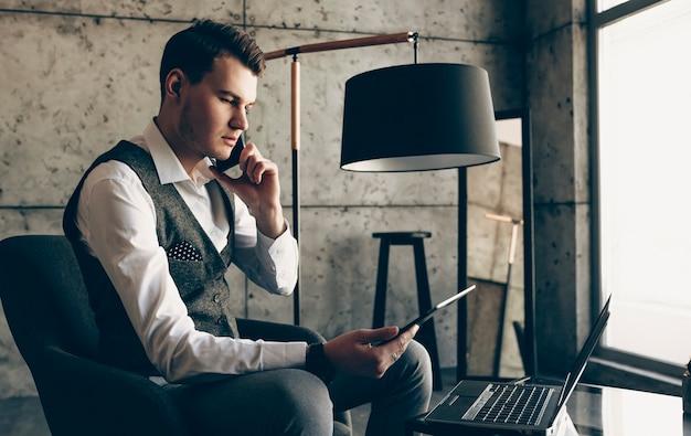 Zijaanzicht portret van een zelfverzekerde stijlvolle jonge zakenman zittend in zijn stoel tijdens het praten op smartphone met een tablet in zijn hand in de buurt van een raam.