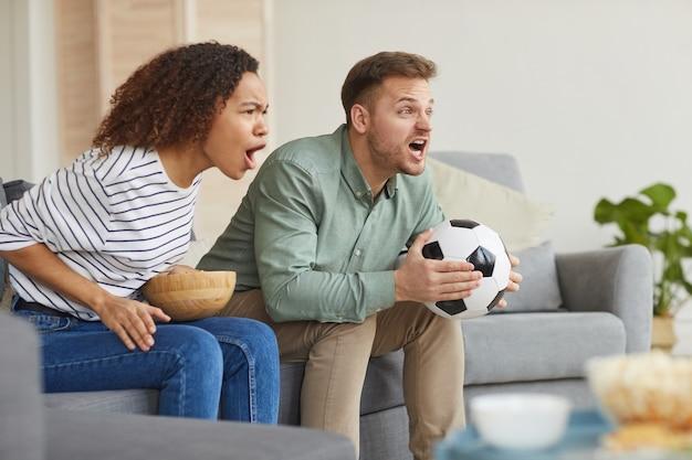 Zijaanzicht portret van emotionele paar kijken naar sportwedstrijd op tv thuis en luid juichen zittend op de bank in gezellig appartement