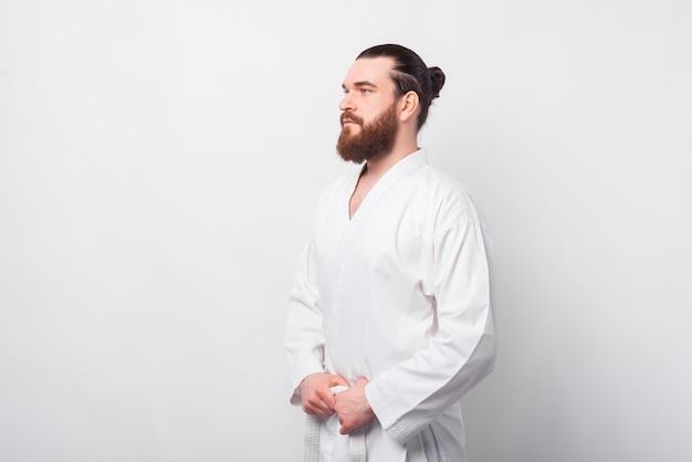 Zijaanzicht portret van ernstige bebaarde man in uniform taekwondo