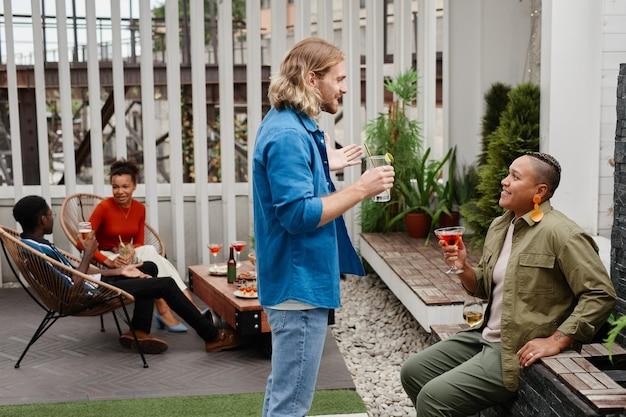 Zijaanzicht portret van glimlachende jonge man die met een vriend praat terwijl hij geniet van een buitenfeest op het dak, kopieer ruimte