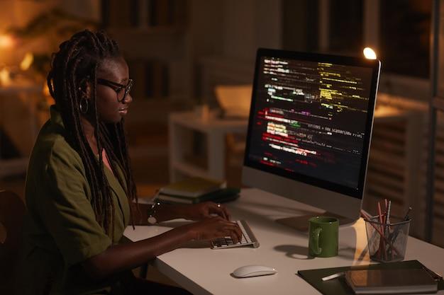 Zijaanzicht portret van hedendaagse afro-amerikaanse vrouw code schrijven en kijken naar computerscherm tijdens het werken in een donkere kantoor, kopieer ruimte