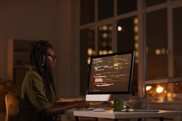 Zijaanzicht portret van hedendaagse afro-amerikaanse vrouw computerscherm kijken en code schrijven tijdens het werken 's avonds laat, kopieer ruimte