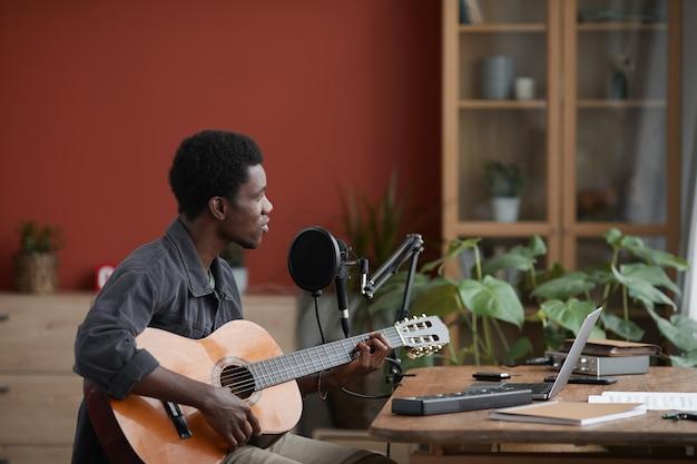 Zijaanzicht portret van jonge afro-amerikaanse man gitaarspelen zittend door microfoon in huis opnamestudio, kopie ruimte