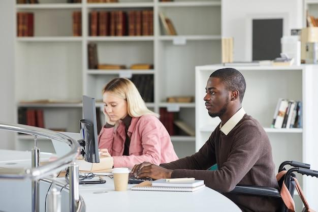 Zijaanzicht portret van jonge afro-amerikaanse man met behulp van computer tijdens het studeren in de universiteitsbibliotheek,