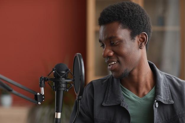 Zijaanzicht portret van jonge afro-amerikaanse man zingen naar microfoon tijdens het opnemen van muziek in de thuisstudio, kopieer ruimte