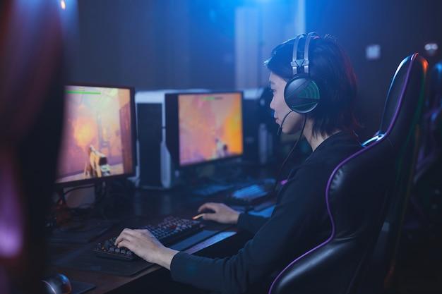 Zijaanzicht portret van jonge aziatische man spelen van videogames en het dragen van koptelefoon in donkere cyber interieur, kopie ruimte