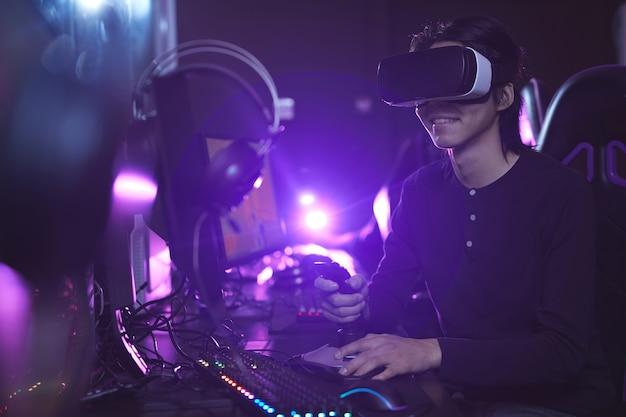 Zijaanzicht portret van jonge aziatische man vr-headset dragen tijdens het spelen van videogames met behulp van race-shift in donkere cyber interieur, kopie ruimte