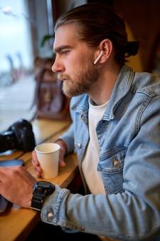Zijaanzicht portret van jonge, bebaarde hipster kerel in koptelefoon werken in café met behulp van laptop, serieus kijken naar kant, in denim casual jasje. ruimte kopiëren