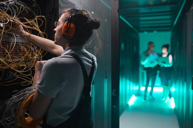 Zijaanzicht portret van jonge netwerkingenieur in serverruimte die onderhoudswerk doet in datacenter, kopieer ruimte