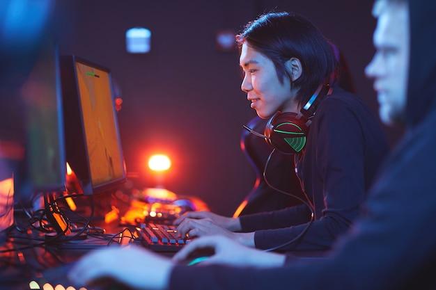 Zijaanzicht portret van lachende aziatische man spelen van videogames met pro cybersport team, kopie ruimte