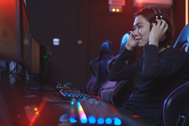Zijaanzicht portret van lachende aziatische man zetten koptelefoon klaar om videogames te spelen in pro-gaming studio, kopie ruimte
