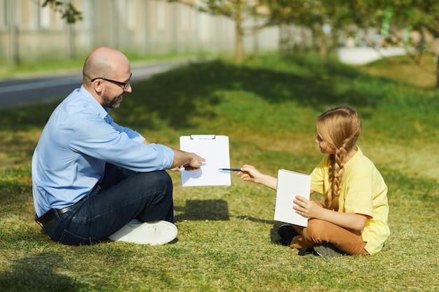 Zijaanzicht portret van lachende volwassen man zittend op groen gras en wijzend op klembord tijdens les uitleggen aan meisje tijdens buiten klas, kopie ruimte