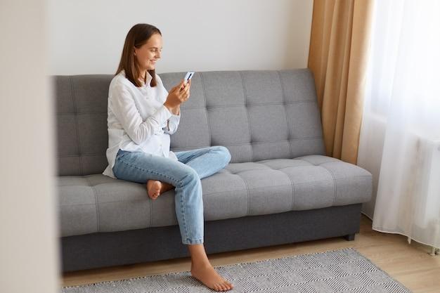 Zijaanzicht portret van lachende vrouw met wit overhemd en spijkerbroek met behulp van mobiele telefoon, kijkend naar apparaatscherm met gelukkige uitdrukking, geweldig nieuws lezend van bericht in sociaal netwerk.