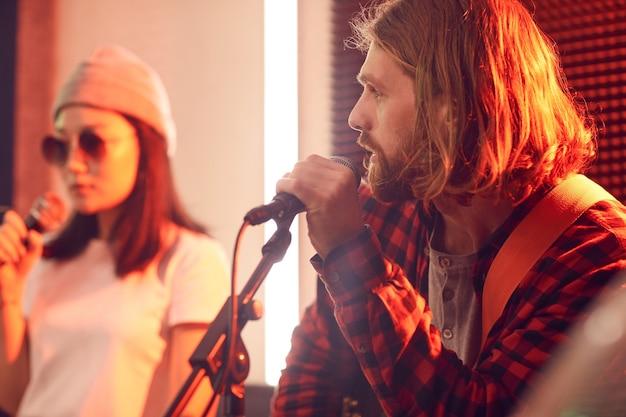 Zijaanzicht portret van langharige jonge man gitaar spelen en zingen naar microfoon tijdens repetitie
