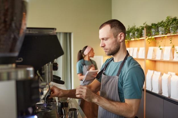 Zijaanzicht portret van mannelijke barista die verse koffie maakt in café terwijl hij een koffiemachine bedient, kopieer ruimte