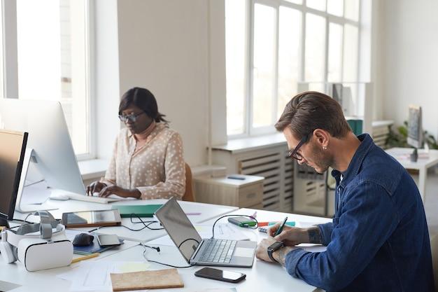 Zijaanzicht portret van mannelijke software-ingenieur die mobiele applicatie of website ontwerpt tijdens het werken met een laptop op kantoor, kopieer ruimte