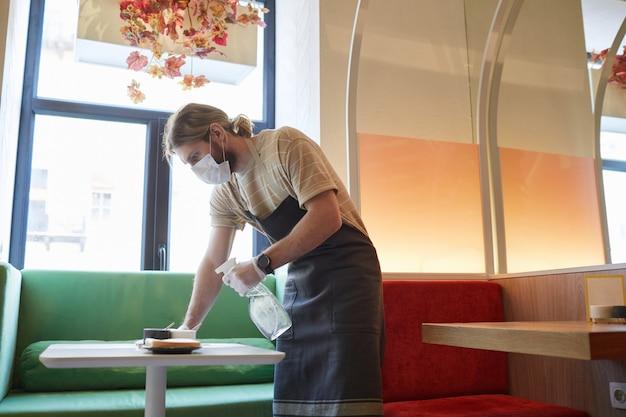 Zijaanzicht portret van mannelijke werknemer die een masker draagt terwijl hij tafels in café ontsmet, kopieer ruimte