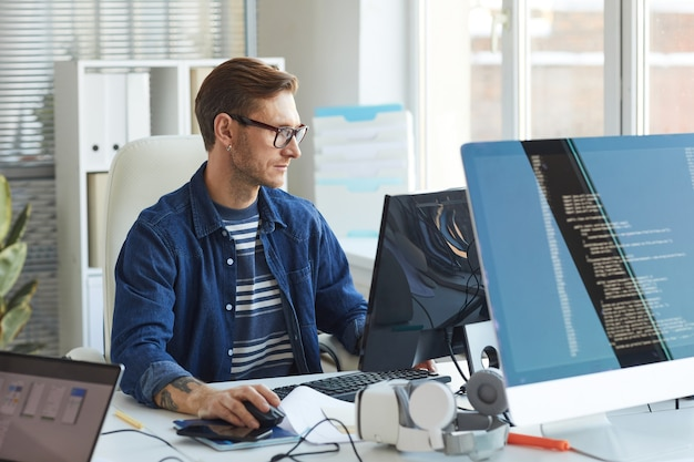 Zijaanzicht portret van moderne it-ontwikkelaar die computer op kantoor gebruikt terwijl hij aan vr-games en software werkt, kopieer ruimte