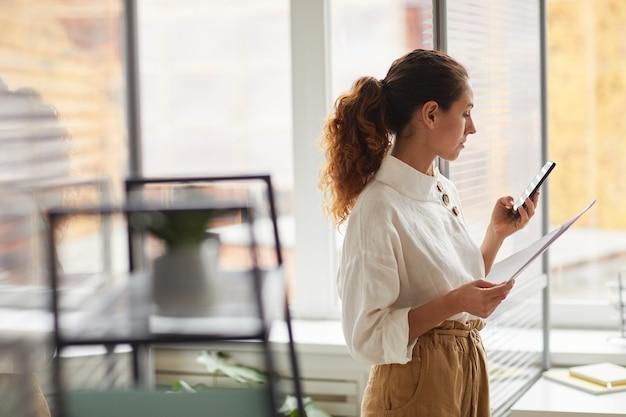 Zijaanzicht portret van moderne succesvolle zakenvrouw smartphone terwijl staande door raam in kantoor, kopieer ruimte