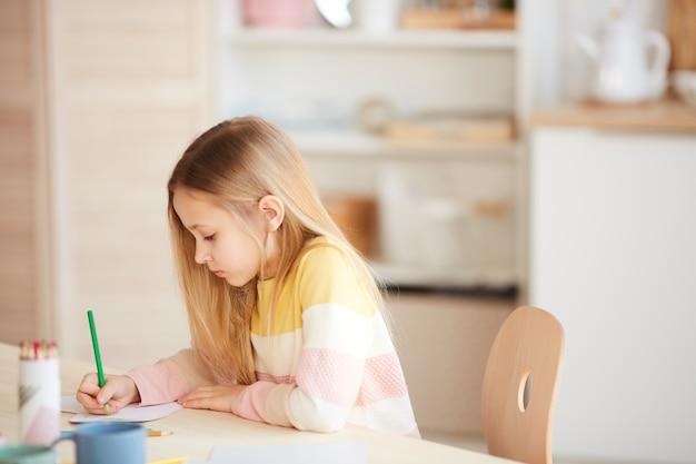Zijaanzicht portret van schattig klein meisje afbeeldingen tekenen of huiswerk zittend aan tafel in interieur, kopie ruimte