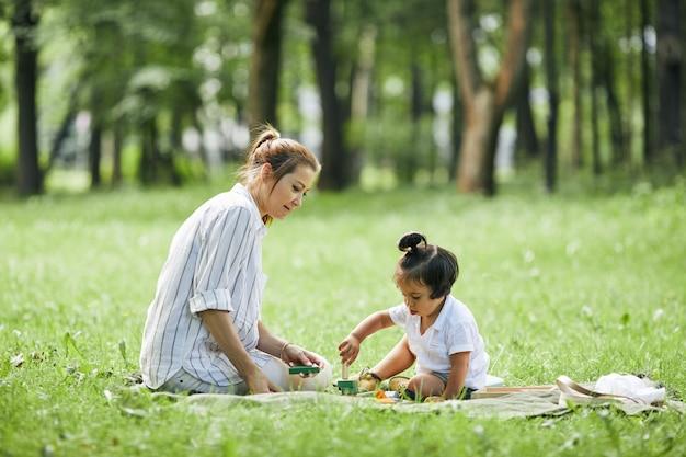 Zijaanzicht portret van schattige kleine jongen met jonge moeder in park samen spelen met speelgoed en genieten...