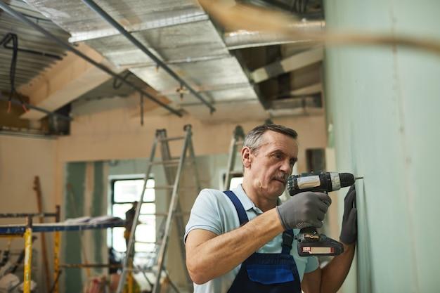Zijaanzicht portret van senior bouwvakker boormuur tijdens het renoveren van huis alleen, kopieer ruimte