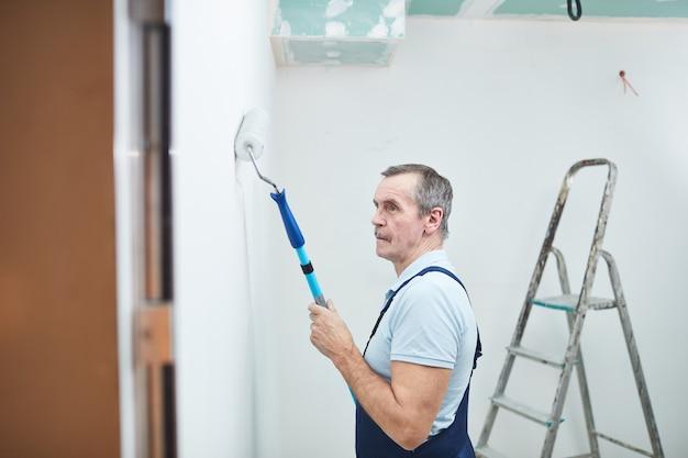 Zijaanzicht portret van senior bouwvakker schilderij muur tijdens het renoveren van huis, kopieer ruimte