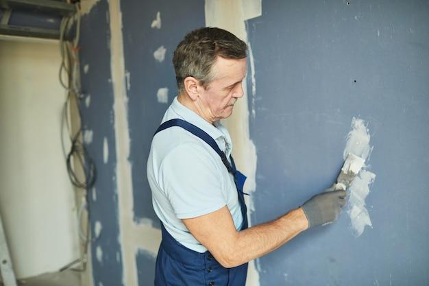Zijaanzicht portret van senior man aan het werk op droge muur tijdens het renoveren van huis, kopie ruimte