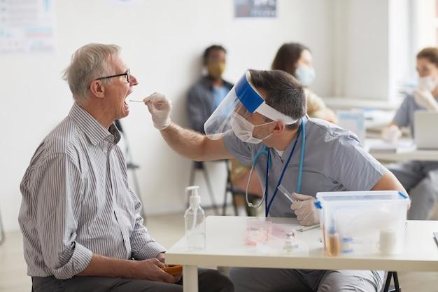 Zijaanzicht portret van senior man die covid-test doet in vaccinatiecentrum of kliniek, kopieer ruimte