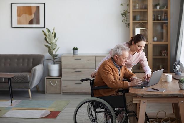 Zijaanzicht portret van senior man in rolstoel met laptop in bejaardentehuis met verpleegster die hem helpt, kopieer ruimte