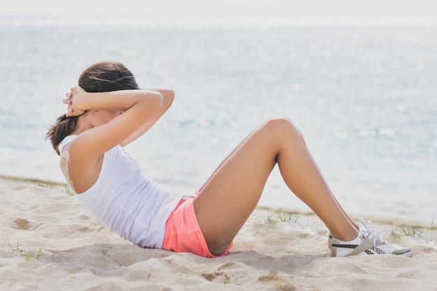 Zijaanzicht portret van sportieve vrouw zitten op het strand