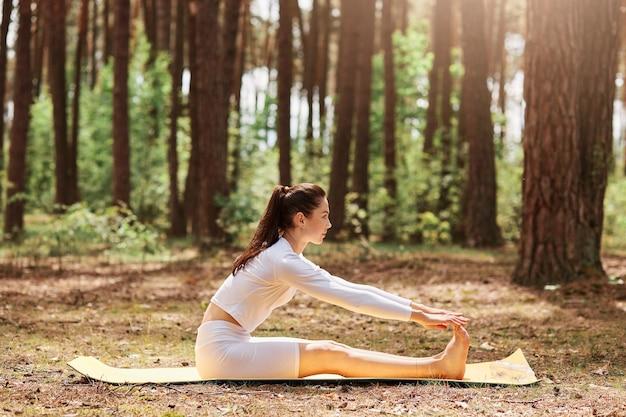 Zijaanzicht portret van sportkleding zittend in sit-up positie in de open lucht, yoga training in het bos, training op de natuur, ontspannen en meditatie, gezonde levensstijl.