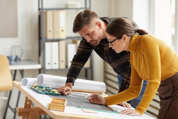 Zijaanzicht portret van twee architecten wijzend op plattegrond tijdens het werken aan blauwdrukken op de werkplek,